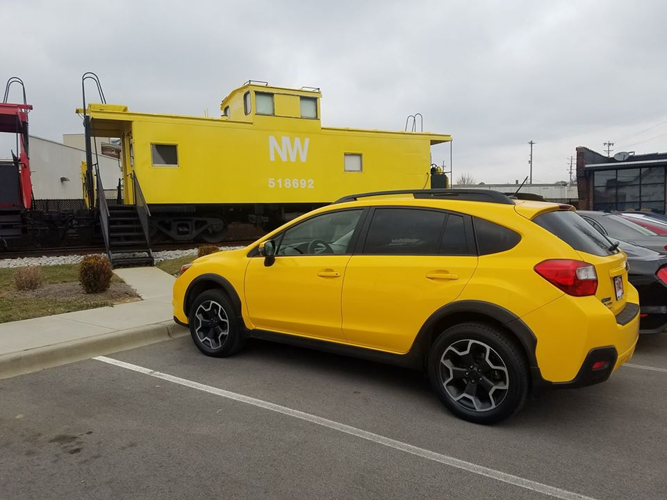 yellow car in front of a yellow caboose